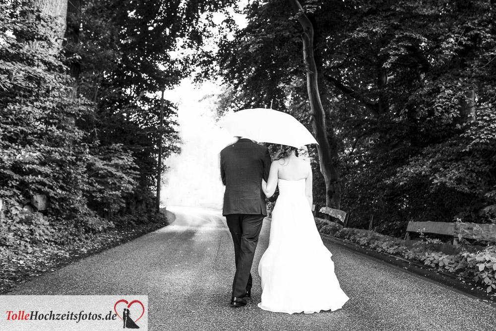 Das Brautpaar mit Regenschirm